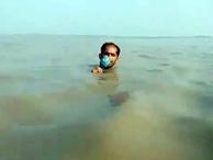 Muhabir sel haberini boğazına kadar gelen suda sundu